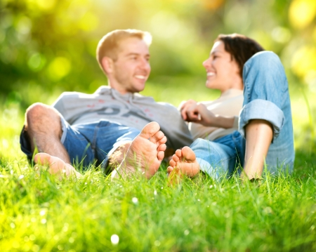 pies masculinos: Park Young Couple Lying on Grass aire libre