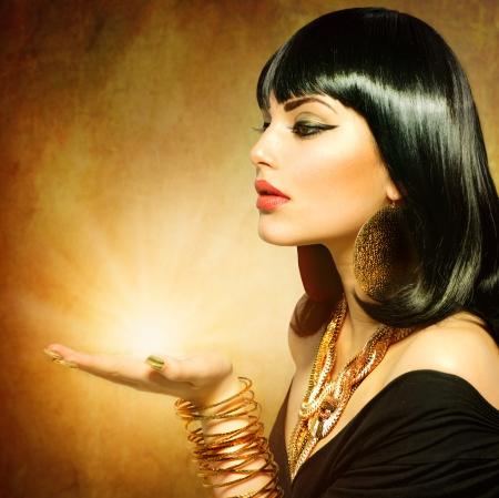 Vrouw in Egyptische stijl met magisch licht in haar hand