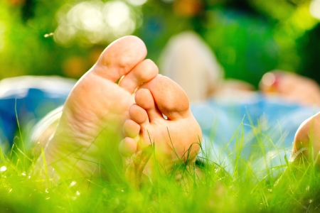 young feet: Park  Young Couple Lying on Grass Outdoor