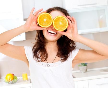 naranjas: Retrato de mujer joven divertido y saludable con naranja sobre los ojos