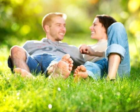 pied fille: Parc jeune couple allong� sur l'herbe en plein air Banque d'images