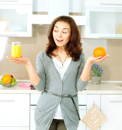 Funny Woman Choosing between Orange Juice or Whole Orange  Stock Photo - 19631889