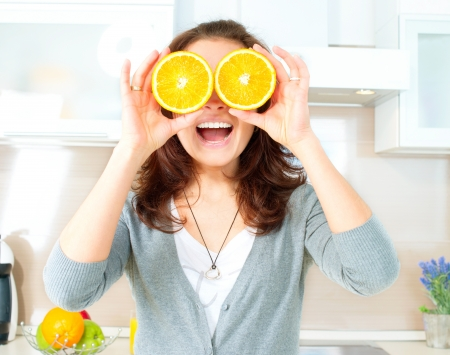 Funny Woman with Orange over Eyes in the Kitchen Stock Photo - 19631884