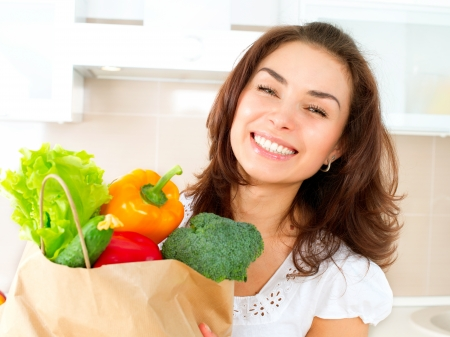 Happy Young Woman with vegetables in shopping bag Stock Photo - 19631898