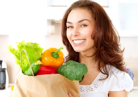 Happy Young Woman with vegetables in shopping bag photo