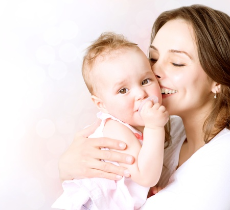 mums: Mother and Baby kissing and hugging  Happy Family  Stock Photo