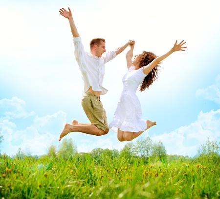 幸せなカップルの屋外の緑の野原に家族をジャンプ
