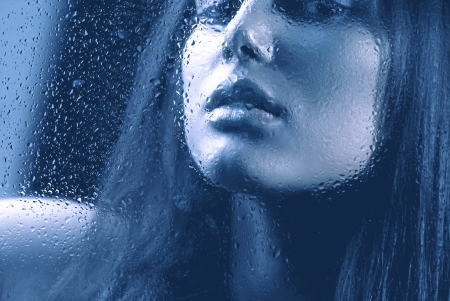Portrait of Beauty Girl behind the Wet Glass  photo