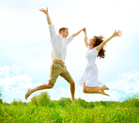 leaping: Happy Couple Outdoor  Jumping Family on Green Field Stock Photo