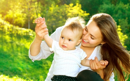 mums: Beautiful Mother And Baby outdoors  Nature Stock Photo