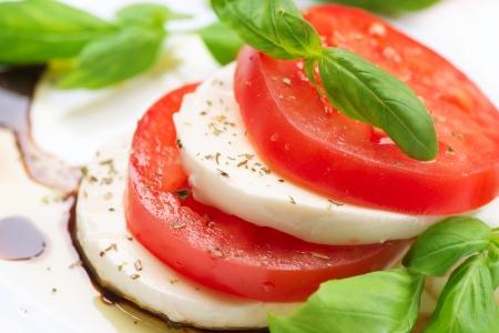 バジルの葉をカプレーゼのサラダ トマトとモッツァレラチーズのスライス 写真素材