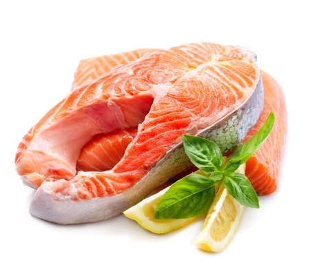 raw fish: Raw Salmon Red Fish Steak with Herbs and Lemon isolated on White  Stock Photo