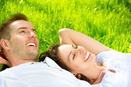 アウトドア: 屋外の芝生の上に横たわって若いカップル 写真素材