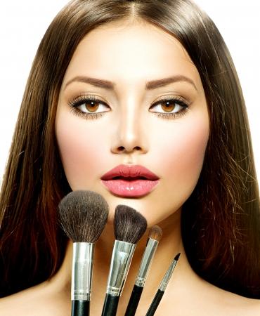 ブルネットの女性の化粧ブラシ メイクアップと美しさの少女