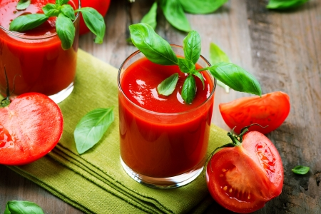 jugo de tomate: Jugo de tomate y tomates frescos con albahaca en una tabla de madera Foto de archivo