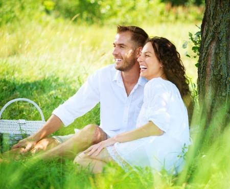 riendo: Pares jovenes que tienen comida campestre en un parque Familia feliz al aire libre Foto de archivo