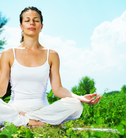 lotus pose: Yoga  Young woman doing yoga exercise outdoor  Stock Photo