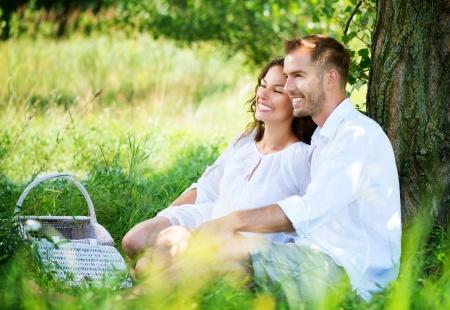 outdoor: Pares jovenes que tienen comida campestre en un parque Familia feliz al aire libre Pareja joven con picnic en un parque Familia feliz al aire libre Foto de archivo