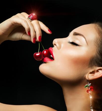 mujeres eroticas: Mujer atractiva que come la cereza Labios rojos sensuales con las cerezas