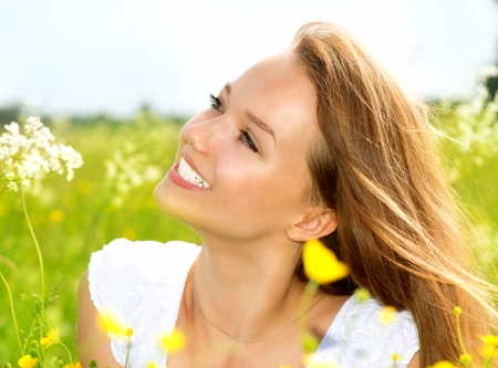 grass: Beauty Girl in the Meadow lying on Green Grass with wild Flowers  Stock Photo