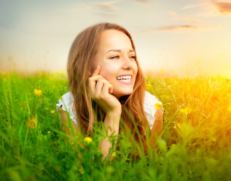 Beauty Girl in the Meadow lying on Green Grass with wild Flowers photo