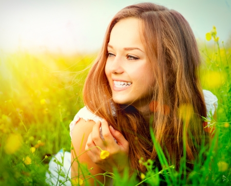 Beauty Girl in the Meadow lying on Green Grass  photo