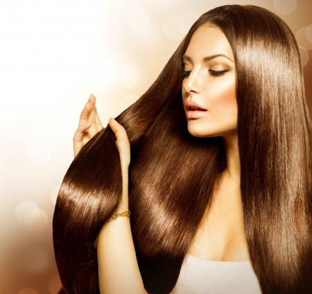 Schoonheid Vrouw wat betreft haar lang en gezond bruin haar Stockfoto