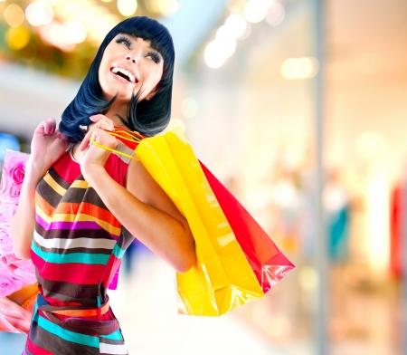 Femme de beauté avec des sacs dans un centre commercial