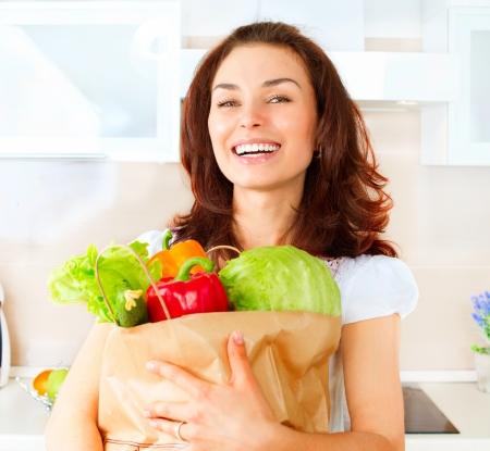 食事概念の買い物袋で野菜と幸せな若い女性