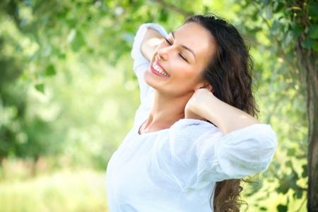 屋外の美しい若い女性は、自然を楽しむ