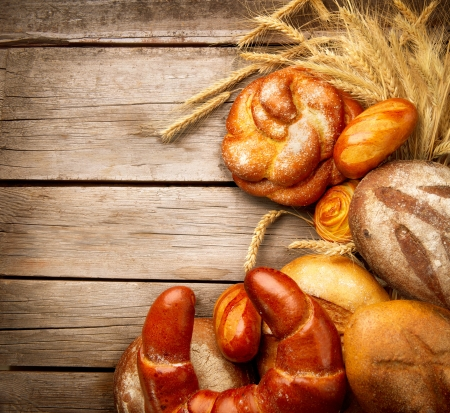 Bakery Bread and Sheaf over Wood Background photo