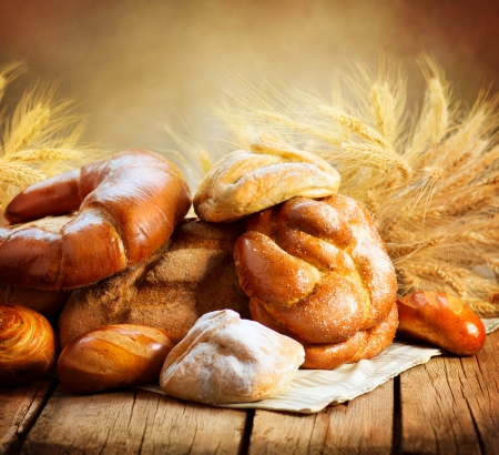 Bakery Bread on a Wooden Table  Various Bread and Sheaf  photo