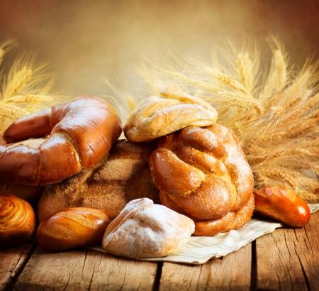dobr�: Pekárna chleba na dřevěném stole Různé chleba a snopu