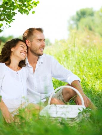 persona feliz: Pares jovenes que tienen comida campestre en un parque Familia feliz al aire libre Foto de archivo