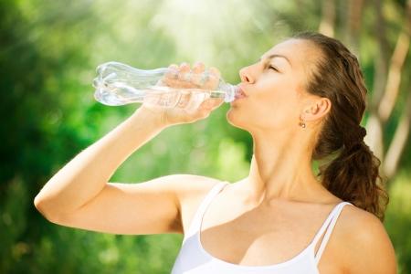 병에서 건강하고 스포티 한 젊은 여성이 마시는 물