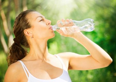 saludable: Sana y deportiva Mujer joven que bebe agua de la botella