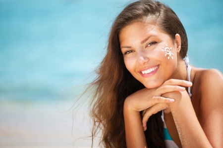 Beautiful happy Girl applying Sun Tan Cream on her Face  Stock Photo