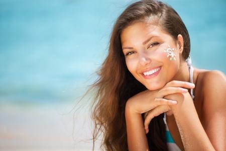 woman happy: Beautiful happy Girl applying Sun Tan Cream on her Face  Stock Photo
