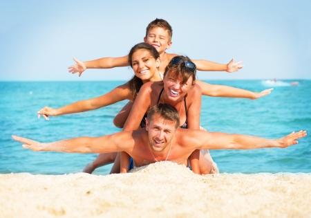 Счастливая семья весело на праздниках лета пляжа Фото со стока