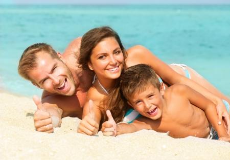 家族: ビーチで楽しい小さな子供と一緒に幸せな若い家族