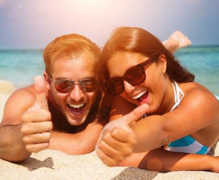 sunglasses: Pareja feliz en las gafas de sol que se divierten en la playa
