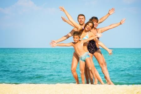 familia viaje: Familia feliz que se divierte en la playa de vacaciones