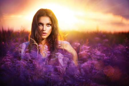 Beauty Girl Lying on a Meadow with Violet Flowers