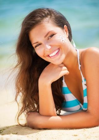 to tan: Beautiful happy Girl applying Sun Tan Cream on her Face