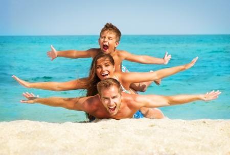 ビーチで楽しい小さな子供と一緒に幸せな若い家族