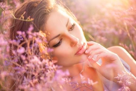 すみれ色の花の草原に横たわっている美しさの少女