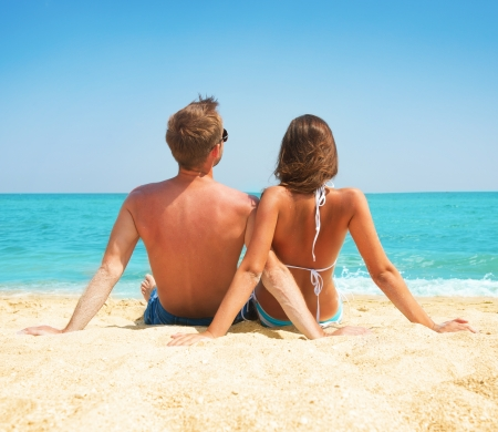 guy on beach: Young Couple Sitting together on the Beach  Vacation concept  Stock Photo