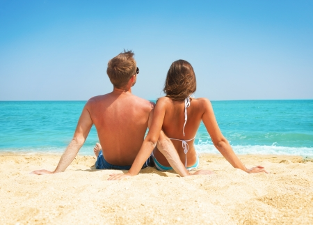 Young Couple Sitting together on the Beach  Vacation concept  Stock Photo