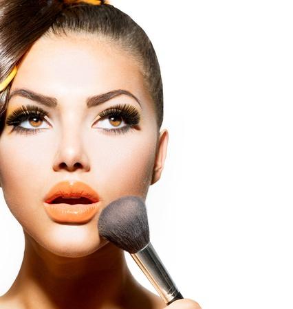 美しい若い女性はブルネットの少女の化粧を適用します。 写真素材