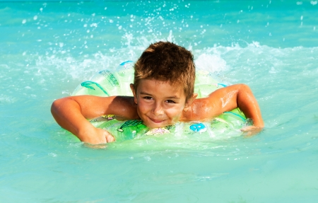 Happy Child Playing in Swimming in Sea  Summer Vacations Concept  photo